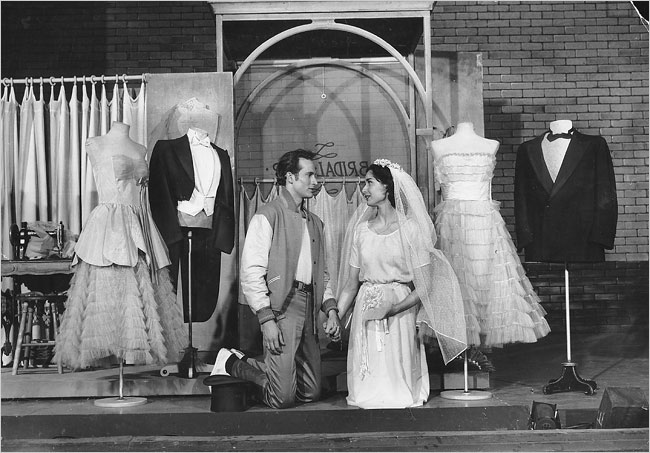 Tony and Maria on their knees, looking longingly into each other's eyes, surrounding by wedding wear.