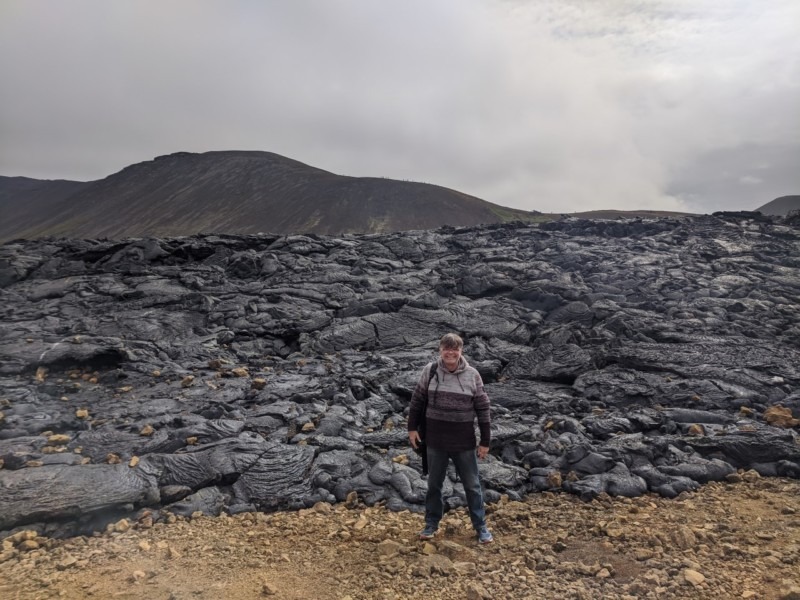 A person standing on a rocky hill  Description automatically generated with low confidence